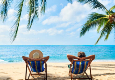 Couple relax on the beach enjoy beautiful sea on the tropical island. Summer beach vacation concept